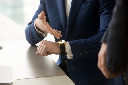 Foto de Close up view of businessman wearing suit pointing on hand expensive luxury wristwatch at meeting, showing unpunctual partner he is being late, punctuality management concept, time is money - Imagen libre de derechos