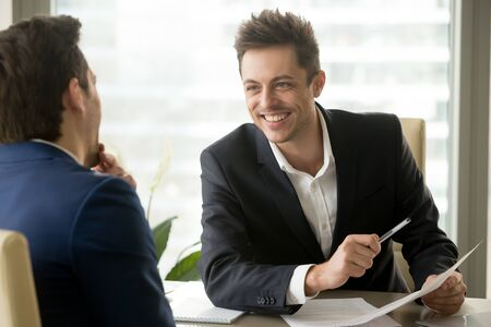Foto de Two smiling positive businessmen discussing new project at meeting, joking and laughing, friendly nice manager consulting client, business partners having fun during discussion, good relationships - Imagen libre de derechos
