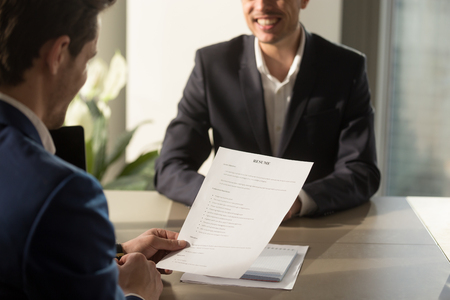 Photo pour Friendly employer conducting job interview, reviewing good resume of prepared skilled smiling applicant waiting for result at background, recruiter considering cv, focus on document, close up view - image libre de droit