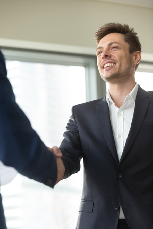 Photo pour Smiling young businessman wearing suit shaking male hand, greeting welcoming handshake at meeting, nice to meet you, good first impression, happy to join business team, thanking for support, vertical - image libre de droit