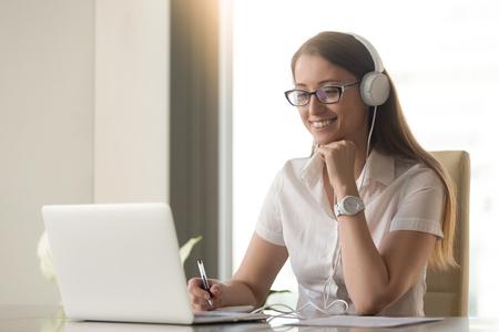 Foto de Smiling happy businesswoman in headphones sits at desk, looks at laptop screen, making notes, participating in self-improvement webinar, having fun on internet, communicating online by video call - Imagen libre de derechos
