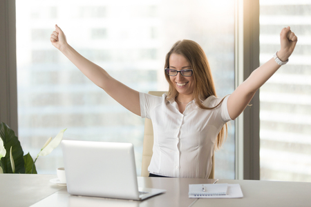 Foto de Excited smiling businesswoman celebrating business success at workplace, raising hands looking at laptop screen, feeling happy about great win, good news online, positive result, passed exam, got job - Imagen libre de derechos