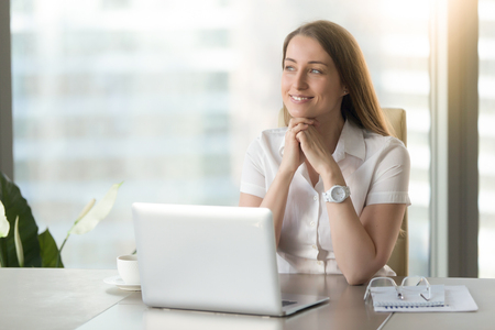 Foto de Meditative smiling businesswoman dreaming of future success at workplace, dreamy hopeful woman looking away, feeling anticipation excitement, having plan, positive thinking and visualization, portrait - Imagen libre de derechos