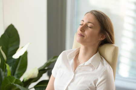 Photo pour Calm attractive woman feeling relaxed in office home, peaceful mindful businesswoman leaning back on chair with eyes closed, meditating at work, taking deep breath to relax, no stress at workplace - image libre de droit