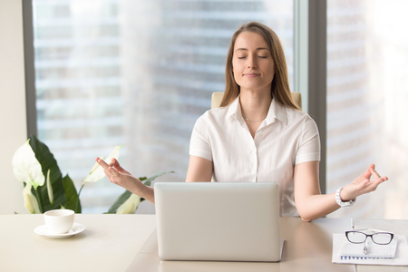 Foto de Mindful businesswoman practices breathing exercises at workplace, peaceful woman enjoys yoga with eyes closed at desk, no stress, keep calm, hands in chin mudra gesture, office meditation, portrait - Imagen libre de derechos