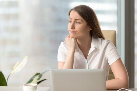 Foto de Discontented thoughtful woman with hand under chin bored at work, looking away sitting near laptop, demotivated office worker feels lack of inspiration, no motivation, boring routine, creative crisis - Imagen libre de derechos