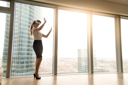 Foto de Excited smiling businesswoman wearing virtual reality glasses, happy woman exploring augmented world, interacting with digital interface while standing near big window of modern office, copy space - Imagen libre de derechos