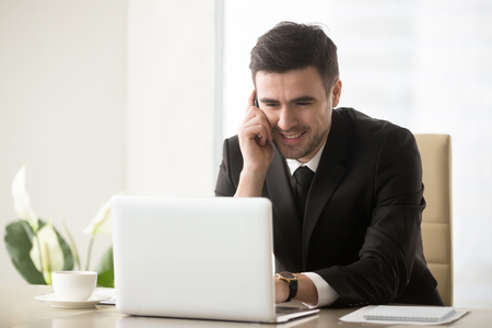Foto de Smiling businessman talking on cellphone sitting at office desk in front of laptop, having successful mobile negotiations with client, manager consulting customer by phone, easy internet banking - Imagen libre de derechos
