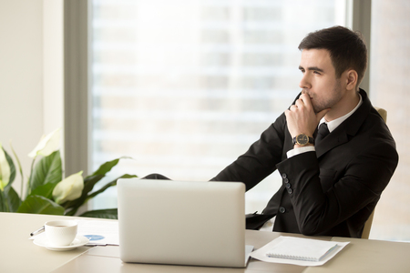 Foto de Thoughtful pensive businessman deep in thoughts looking away sitting near laptop at workplace, successful entrepreneur thinking over new ways to improve business, future perspectives, managing risks - Imagen libre de derechos