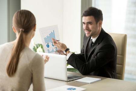 Photo pour Happy project manager holds financial report, shows rising stats and growing graphs to colleague, satisfied with great development rate, successful strategy, business growth, company success concept - image libre de droit