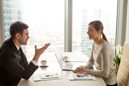 Photo for Enthusiastic businessman and businesswoman discussing company business, talking about new project, sharing ideas during meeting sitting at office desk near big window with urban cityscape, side view - Royalty Free Image