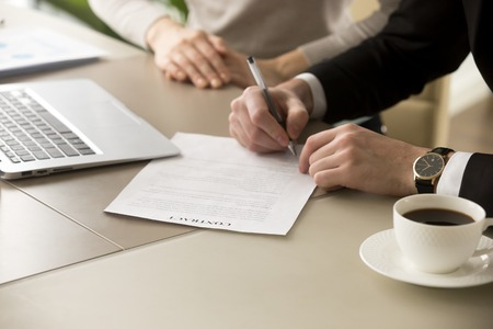 Photo pour Businessman in suit puts signature on contract at business meeting after negotiations with businesswoman, male hand signs official document, subscribes name on legal binding agreement, close up view - image libre de droit
