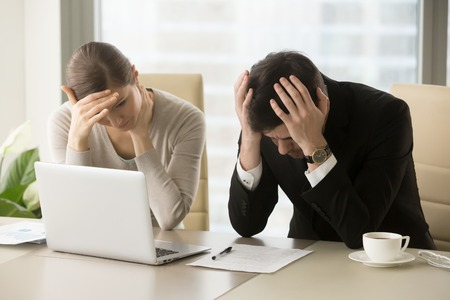 Foto de Tired frustrated business people feeling stressed, upset executives sitting near laptop, holding head in hands, worried about business problem failure, depressed by bad news, company bankruptcy - Imagen libre de derechos