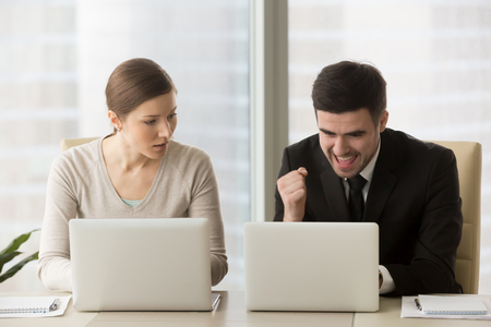 Photo pour Resentful employee loser looks enviously at promoted colleague winner enjoying success, good news while working on laptop, feels jealous about rivals achievements, team rivalry, unfair competition - image libre de droit