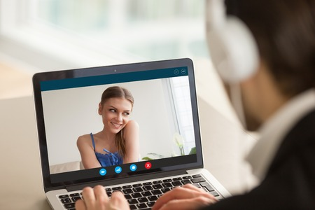 Foto de Shy teen girl on video call with boyfriend, couple talking by videoconferencing app, young woman embarrassed during virtual chat with man, distance relationships, focus on screen, close up rear view - Imagen libre de derechos