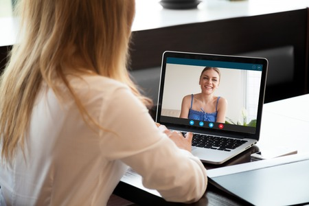 Photo pour Two young women chatting online by making video call on laptop, using videoconferencing app for communication with distance friend, studying online course, virtual learning, close up rear view - image libre de droit