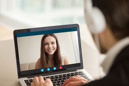 Foto de Smiling girl on videocall with guy, making video call to close foreign friend, talking by web camera, using virtual chat app online, long distance relationships, focus on screen, close up rear view - Imagen libre de derechos