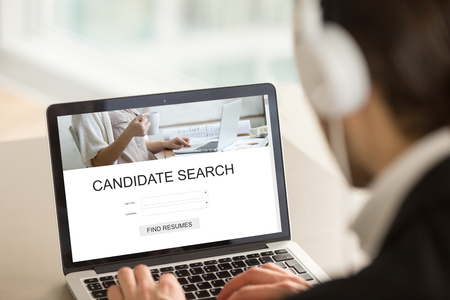 Photo for Employer searching candidates for part or full time job on internet web service, headhunter using laptop, looking for experienced professionals, choosing best staff, find resumes, close up rear view - Royalty Free Image