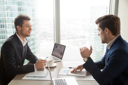 Photo pour Two businessmen discussing company financial strategy or marketing research during meeting at desk in office. Business partners deciding how to improve profitability and accelerate investments return - image libre de droit
