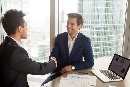 Photo for Smiling CEO in stylish blue business suit handshaking with partner while sitting at desk with laptop and documents. Boss welcoming company new employee. Financial advisor meeting with client in office - Royalty Free Image