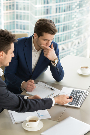 Photo for Business partners using laptop while working together on important corporate project in office. Businessman attentively listening to adviser Investment specialist making presentation of promising deal - Royalty Free Image