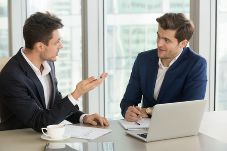 Photo for Businessman explaining his offer to business partner while sitting at desk in office, telling about benefits of cooperation and efforts pooling, discussing prospects of agreement, convincing investor - Royalty Free Image