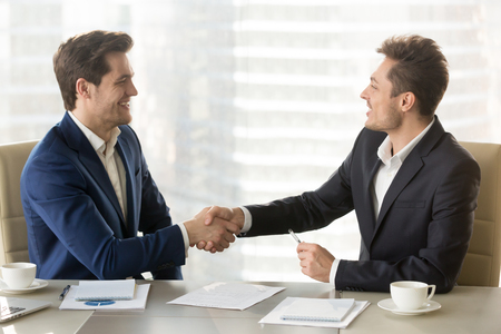 Photo for Happy smiling business partners shaking hands and congratulating each other after singing contract, successful negotiations, profitable partnership, trust between company leaders, conclusion agreement - Royalty Free Image