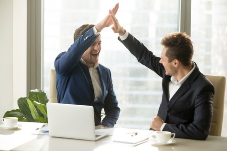 Foto de Excited businessman smiling and giving high five to his business partner or colleague while sitting at meeting table in office. Happy entrepreneurs celebrating success, congratulating with achievement - Imagen libre de derechos