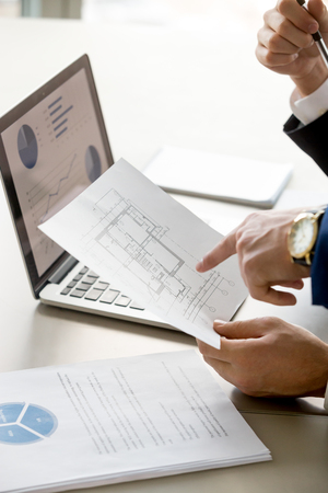 Foto de Close up image of apartments or house plan in businessman hand, laptop with diagrams on screen on background. Real estate agent discussing value of property. Architects planning construction budget - Imagen libre de derechos