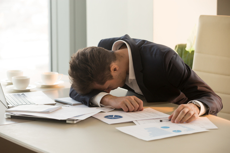 Foto de Tired businessman sleeping at workplace covered with documents. Overworked frustrated entrepreneur dozing, giving up after hard work day. Stressed CEO lying on desk shocked because of business failure - Imagen libre de derechos
