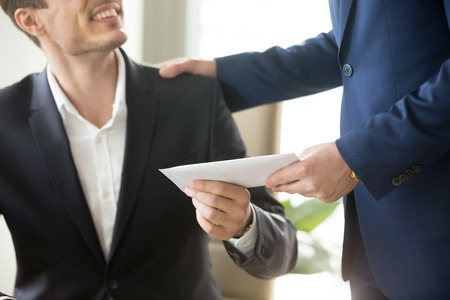 Photo pour Company leader giving money bonus in paper envelope to happy smiling office worker, congratulating employee with increasing of salary or promotion, thanking for successes in work. Close up concept - image libre de droit