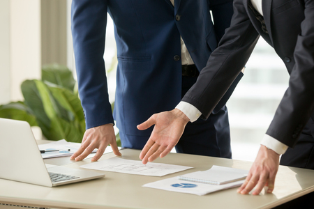 Photo pour Businessman pointing on apartments drawings lying on desk during construction project presentation. Architect or realtor discussing house plan with client. Internal space planning. Close up image - image libre de droit