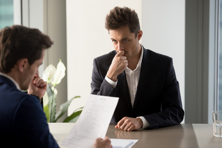 Photo for Nervous male job candidate looking with worriment on human resources generalist reading his resume during interview in company office. Millennial man trying to find job, giving application for vacancy - Royalty Free Image
