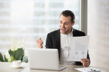 Photo pour Happy handsome project manager in office celebrates and screams with happiness, looking at laptop screen and holding positive financial report. Great news on stock investment, finance victory concept. - image libre de droit