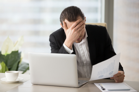 Photo pour Stressed unhappy young businessman in office in front of laptop, holding financial document and facepalming in disbelief because of failing report statistics. Fall in liquidity of stocks, finance loss - image libre de droit