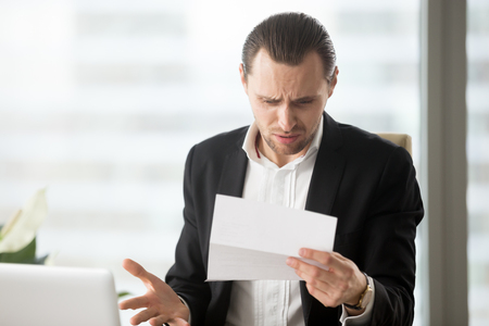 Foto de Frustrated young businessman in suit looking at confusing letter in modern office setting. Unexpected high bill, unpaid debt, failing financial report, tax delinquency, breach of contract concept. - Imagen libre de derechos