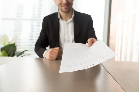 Photo pour Smiling job applicant in suit handing over resume to recruiter during interview. Modern office setting. Recruitment manager giving resume back to candidate. Human resources, hiring, interview concept. - image libre de droit