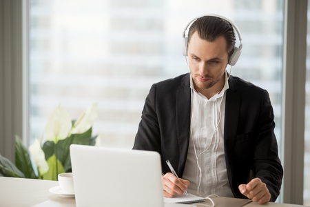 Photo pour Thoughtful businessman in headphones taking notes in front of laptop at workplace. Young manager participating in online meeting or conference, remote job interview, learning foreign languages. - image libre de droit