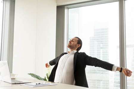 Foto de Smiling businessman stretching his back and arms at the desk at workplace in modern office with window behind. Taking a break from workflow, relaxing, being done with work, finished project concept. - Imagen libre de derechos