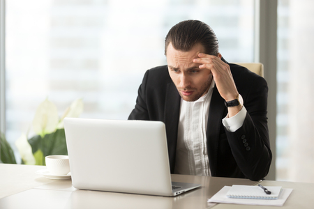Photo for Upset confused businessman looking at laptop screen at workplace in modern office. Stressed young CEO at work desk looking at computer in disbelief about failing report statistics, bad mistake made. - Royalty Free Image