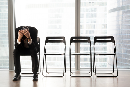 Photo pour Stressed upset businessman sitting on chair, in waiting room, received bad news. Devastated CEO fired by his boss because of failed business project. Job candidate received refusal from HR department. - image libre de droit