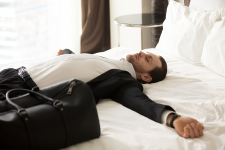 Foto de Exhausted young businessman laying with outstretched arms on bed next to small suitcase in hotel room. Entrepreneur tired after traveling, jet lag. Relieved business worker resting after long flight. - Imagen libre de derechos