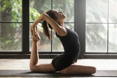 Photo for Young woman practicing yoga, stretching in One Legged King Pigeon exercise, Eka Pada Rajakapotasana pose, working out, wearing sportswear, black shorts and top, indoor full length, home background - Royalty Free Image