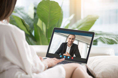 Foto de Young woman sitting on sofa communicates with man in formal suit via video call application. Couple chatting. Long distance relationship, virtual communication concept. Close up view, focus on screen. - Imagen libre de derechos