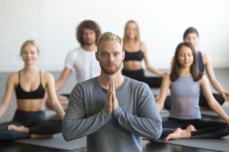 Foto de Group of young sporty people practicing yoga lesson with instructor, sitting in Sukhasana exercise, Easy Seat pose, friends working out in club, focus on male student, making mudra gesture, studio - Imagen libre de derechos