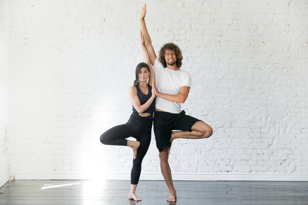Foto de Couple of young sporty people practicing yoga lesson with partner, smiling man and woman standing in Vrksasana exercise, Tree pose, working out, indoor full length, studio. Wellbeing, wellness concept - Imagen libre de derechos