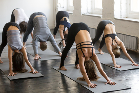 Foto de Group of young sporty attractive people practicing yoga lesson with instructor, stretching in Downward facing dog exercise, adho mukha svanasana pose, friends working out in club, full length, studio - Imagen libre de derechos
