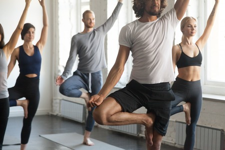Foto de Group of young sporty people practicing yoga lesson with instructor, standing in Vrksasana exercise, Tree pose, working out, indoor close up image length, studio. Wellbeing, wellness concept - Imagen libre de derechos