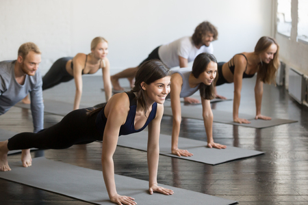 Foto de Group of young sporty attractive people practicing yoga lesson with instructor, doing Push ups or press ups exercise, standing in Plank pose, friends working out in club, indoor full length, studio - Imagen libre de derechos