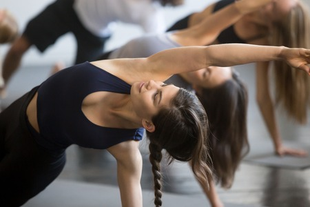 Foto de Group of young sporty people practicing yoga lesson with instructor, stretching in Bending Side Plank exercise, Vasisthasana pose, working out, indoor close up image, studio, smiling woman in focus - Imagen libre de derechos